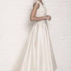 Dress by Muscat Bridal. Corded lace top with applique cap sleeves and mini peplum. Silk organza waterfall skirt with tulle underskirt.