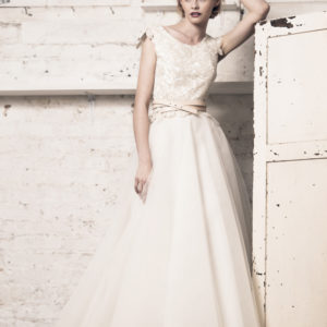 Dress by Muscat Bridal. Corded lace top with applique cap sleeves and mini peplum. Tulle ball skirt.