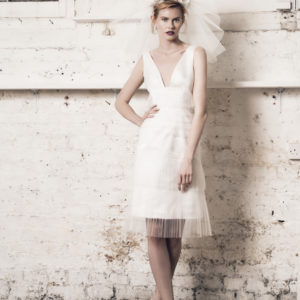 Dress by Muscat Bridal. Knee length dress with layers of pleated tulle and lace.