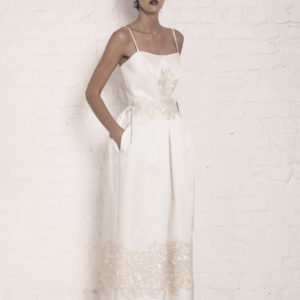 Dress by Muscat Bridal. Silk duchess dress with pleated skirt and corded lace applique.